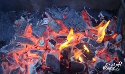 3.Разжигаем в мангале костер и сжигаем дрова. Для приготовления шашлыка из свиных ребрышек следует использовать дрова лиственных деревьев. Прекрасно подойдут поленья яблони и черемухи. После того, как дрова прогорят, разравниваем угли. Не прогоревшие остатки дерева удаляем.
