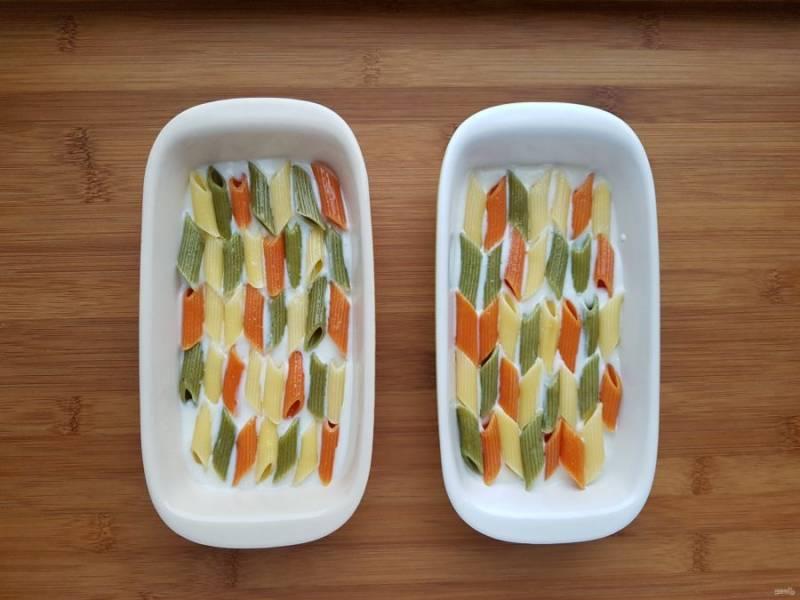 Выложите макароны поверх соуса ровным слоем.