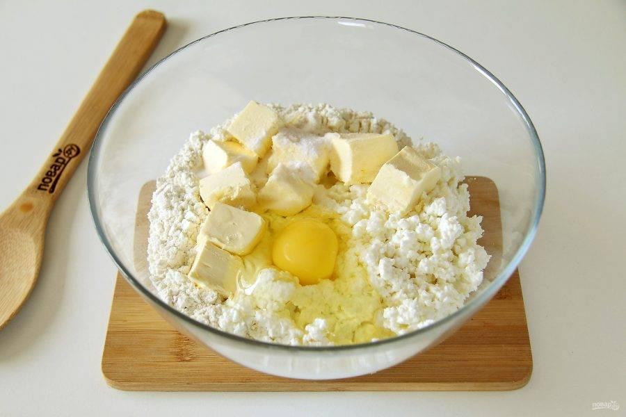 В глубокой миске соедините муку, творог, размягченное сливочное масло, нарезанное кубиками, одно яйцо, соль и соду.