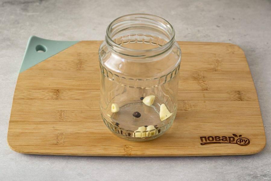 В чистую стерилизованную банку выложите очищенный чеснок и перец горошком.