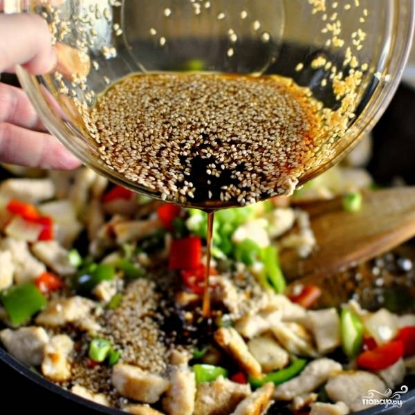 Через 30 секунд после совместного обжаривания курицы и овощей вводим в сковороду кунжутный соус.
