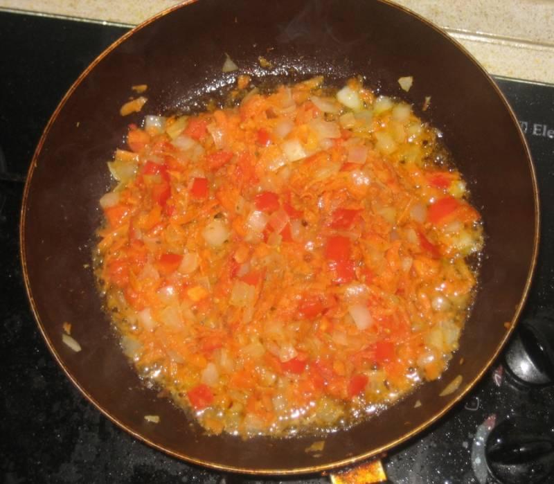 Теперь наливаем в сковороду растительное масло и нагреваем его, выкладываем в масло лук и жарим до золотистого цвета. После этого добавляем к луку тертую на крупной терке морковь, жарим все еще 3 минуты, а затем выкладываем на сковороду нарезанный помидор, обжариваем овощи минут 5, затем выключаем огонь.