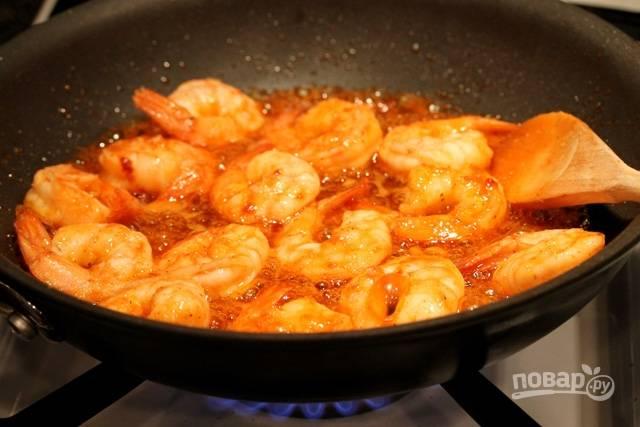 Влейте остро-сладкий соус к креветкам, когда они  уже почти будут готовы. Обжарьте их, помешивая, в течение двух минут.