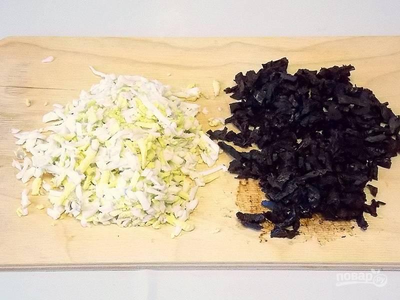 Чернослив вымойте и залейте кипятком на 15 минут. Слейте воду, обсушите его и порежьте соломкой. Натрите яйца на крупной терке.