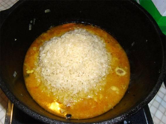 11. С риса слить воду и отправить его в казан. Аккуратно разровнять.