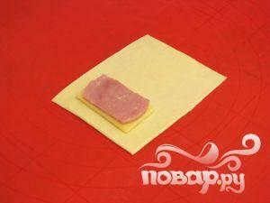 Выложить по ломтику ветчины и сыра на каждый прямоугольник.