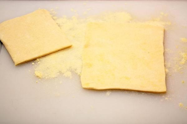 Тесто заранее размораживаем. На стол высыпаем муку и и выкладываем листы. Раскатываем их и нарезаем прямоугольниками.