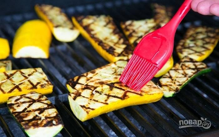 6.Разожгите мангал и выложите кабачки той стороной, что смазали, обжаривайте их с одной стороны около 5 минут, затем переверните.