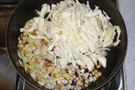 Разогрейте сковородку, налейте в нее растительное масло, обжарьте лук, добавьте к нему капусту, залейте смесь половиной стакана воды и потушите минут 10.