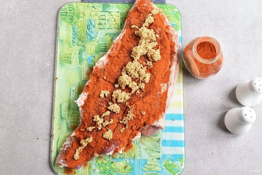 Обсыпьте мясо пряностями и паприкой. Сверху выложите горчичное семя. Предварительно его нужно заварить кипятком и дать остыть. Можно взять готовую зерновую горчицу, но тогда мясо будет слегка кислить. Равномерно распределите все по мясу.