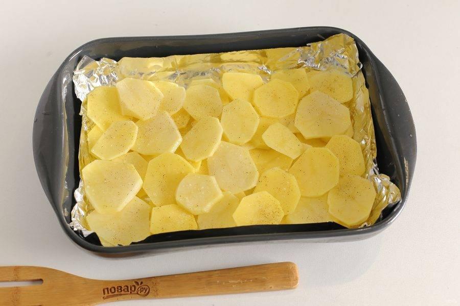 Форму для запекания смажьте маслом (я предварительно застилаю еще форму фольгой). Картофель нарежьте тонкими кружочками и разделите на две части. Часть картофеля выложите в жаропрочную форму, оставляя небольшое количество для второго слоя. Картофель слегка присыпьте перцем и солью. Добавляя соль, учтите, что картофель будет заливаться уже соленой подливой, поэтому не переборщите с этой специей.
