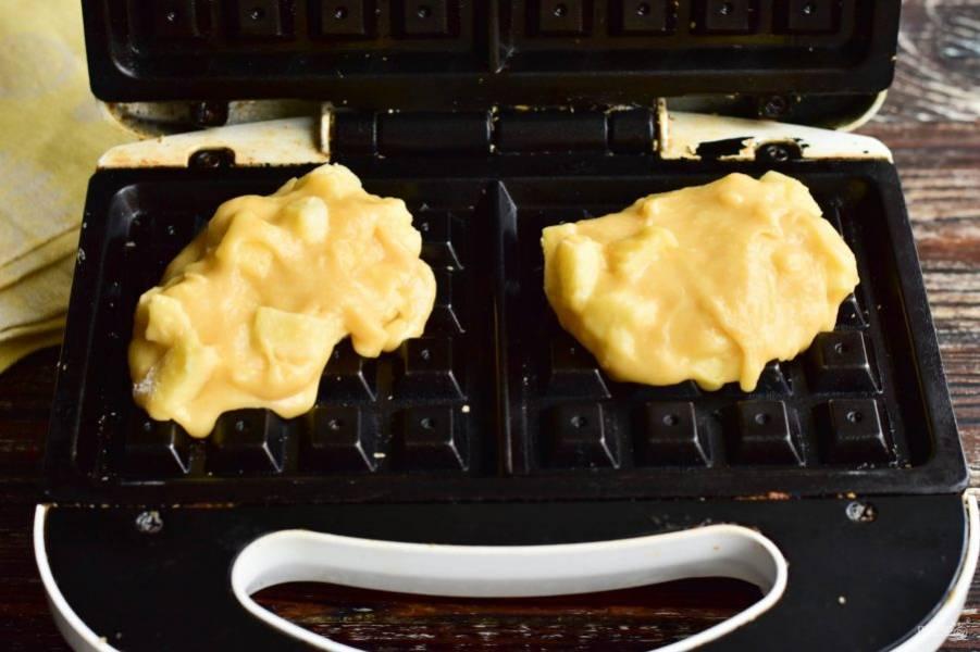 На разогретую вафельницу выложите по 1 ложке теста на каждую половину.