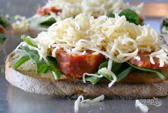 2.На терке натрите твердый сыр, посыпьте им каждый кусочек хлеба.