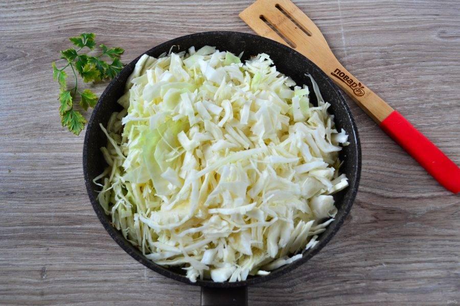 Когда сало достаточно растопится, отправьте в сковороду капусту и жарьте на среднем огне 15-20 минут, не забывая помешивать.