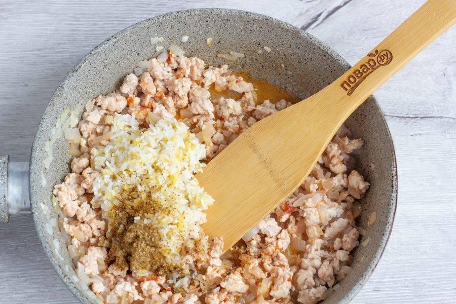 С крупы слейте воду. Выключите плиту, добавьте в фарш любимые специи и крупу. Всё тщательно перемешайте. Можно добавить зелень. Посолите и поперчите по вкусу.
