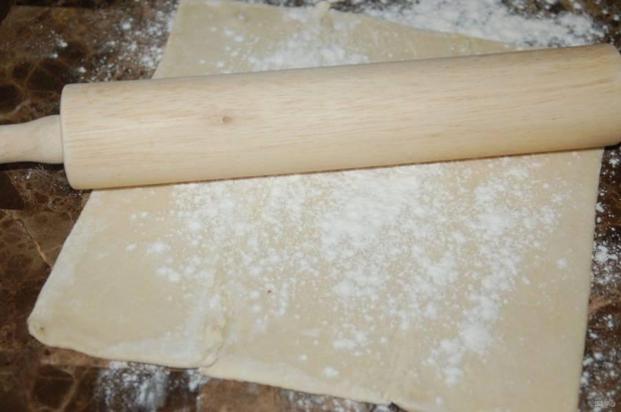 4.Слоеное тесто заранее достаю из морозилки и размораживаю при комнатной температуре. Скалкой раскатываю его в тонкий пласт.