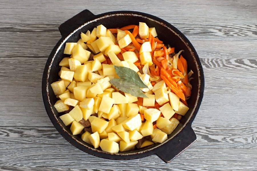 По истечении времени добавьте в жаровню картофель, репу, обжаренные лук и морковь, лавровый лист. Влейте еще 3 ст. горячей воды. Варите под крышкой 30 минут. Огонь чуть ниже среднего.