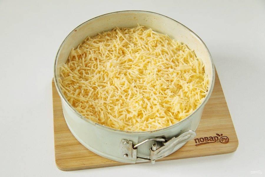 Вылейте на начинку оставшееся тесто и разровняйте его ложкой. Сверху посыпьте немного тертого сыра.
