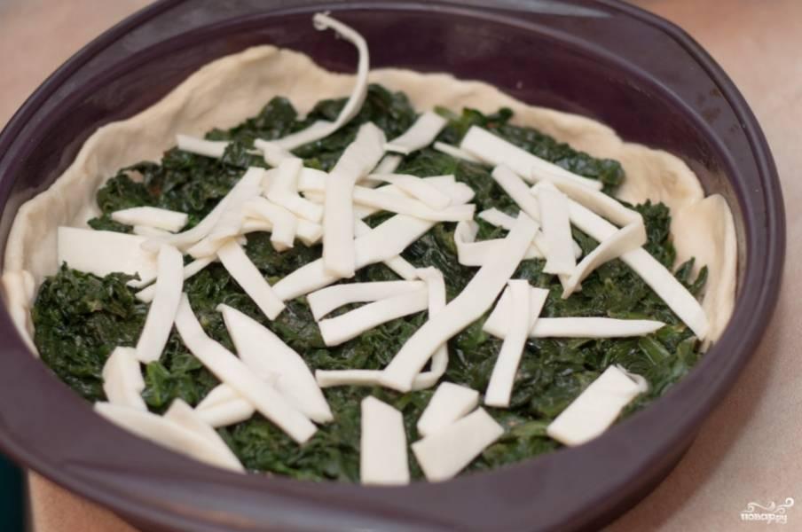 Тесто готовое разделите на 2 части. Одну часть раскатайте и выложите в форму для выпекания. Выложите равномерно сначала шпинат, потом сыр.