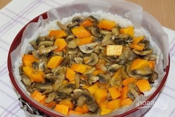 Выложите на рисовую основу начинку и выпекайте пирог в заранее нагретой до 180 градусов духовке около 20 минут.