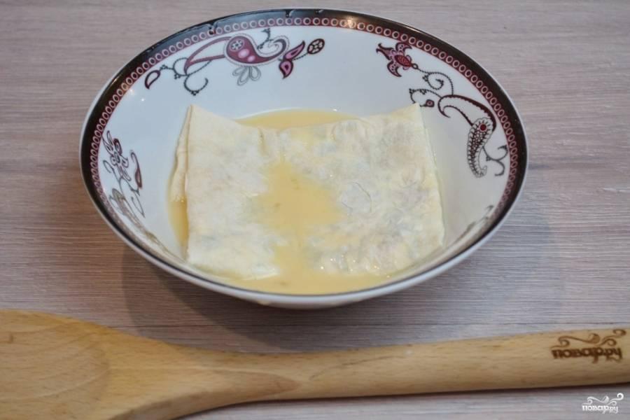 Каждый конвертик окуните в кляр. После выложите на горячую сковороду с растительным маслом. Обжарьте лаваш в кляре с двух сторон (по минуте с каждой стороны).