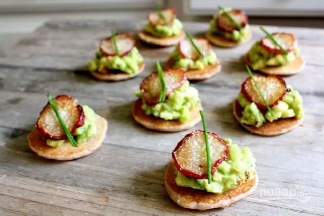 Итак, собираем тарталетку: на оладий кладем немного пасты из яблока и авокадо, а сверху кладем кружочек редиски. Дополняем по желанию зеленью. Получается вот такая красота.