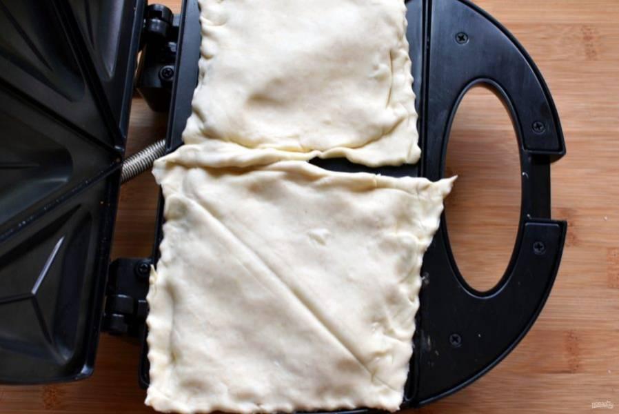 Выложите получившиеся пирожки в сендвичницу, закройте и пеките минуты 3-4 до ровного золотисто-коричневого цвета слоек.