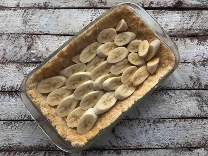 Тесто выложите в форму для выпекания, сделав бортики. Сверху теста выложите нарезанный банан.