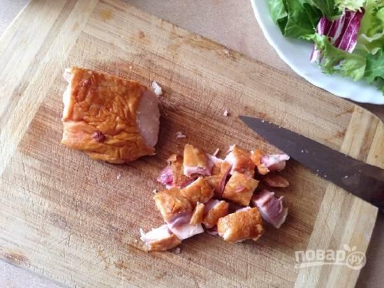 Нарежем копченую курицу кусочками, разложим её поверх салатных листьев.