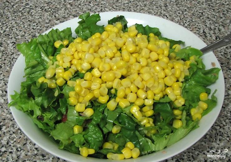 3. Салат промоем, отряхнем от капелек воды и порвем мелкими кусочками. Добавим к салату вместе с кукурузой. Ее, кстати, тоже тщательно отцедите, чтобы в салат не попало много жидкости.