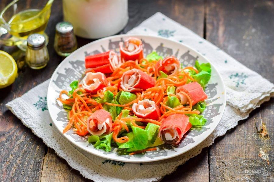Крабовые палочки нарежьте и переложите в салат. Заправьте маслом и лимонным соком, добавьте соль и перец, подавайте к столу.