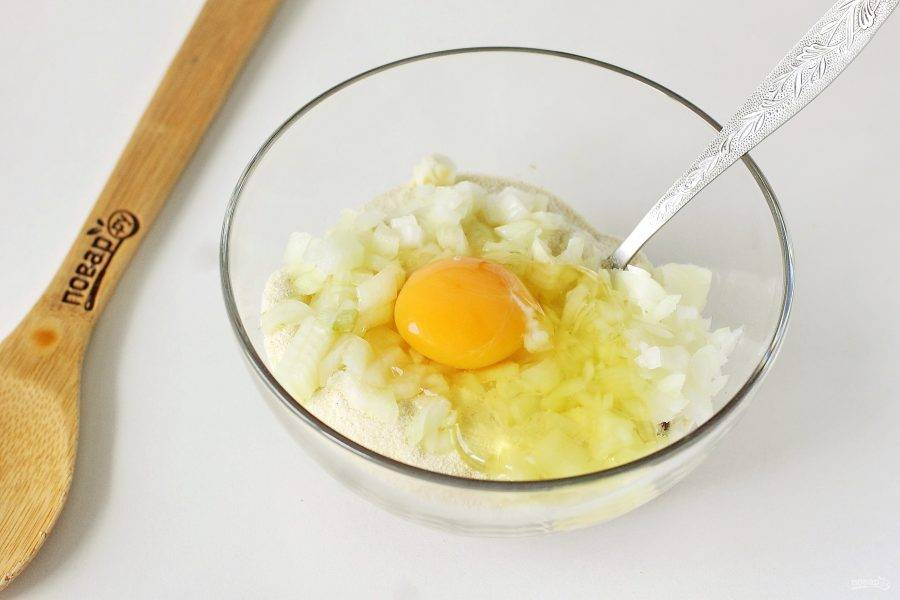 Добавьте нарезанный кубиками лук, манку и яйцо.