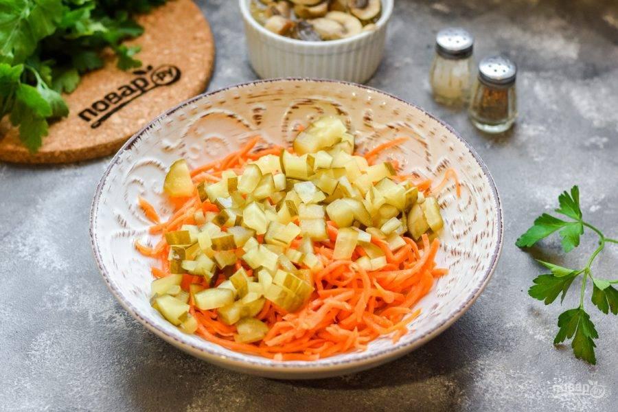Квашеные огурцы нарежьте небольшими кубиками и добавьте в емкость к моркови.