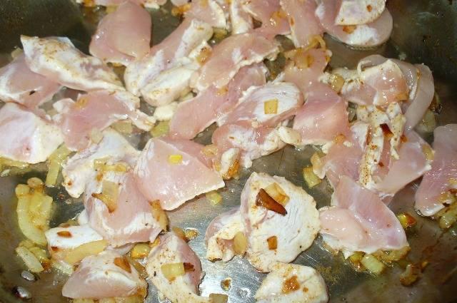 Куриное филе моем и нарезаем небольшими кусочками. Отправляем на сковородку к луку и обжариваем минут 5. Солим и перчим.