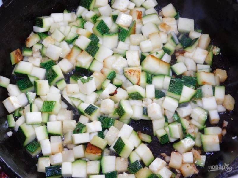 Кабачки нарежьте кубиками и обжарьте вместе с измельченным чесноком.