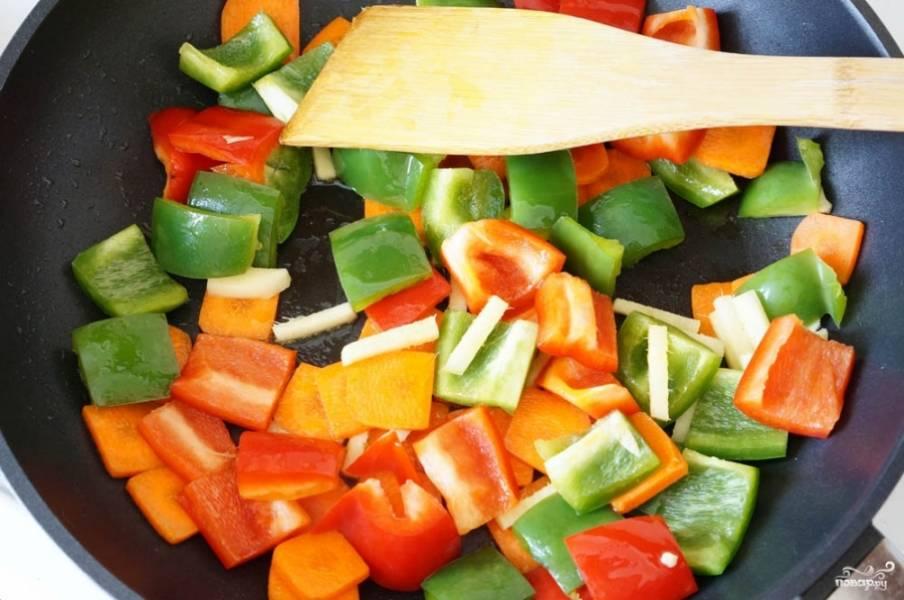 Перец нарежьте одинаковыми квадратиками. Если получится, используйте для блюда перец разных цветов, это будет выглядеть очень красиво. Имбирь почистите и порежьте соломкой. Морковь нарубите кружочками или квадратиками. Чили нарежьте слайсами. Если любите блюда поострее, то не удаляйте из перца семена. Обжаривайте все овощи в сковороде на растительном масле.