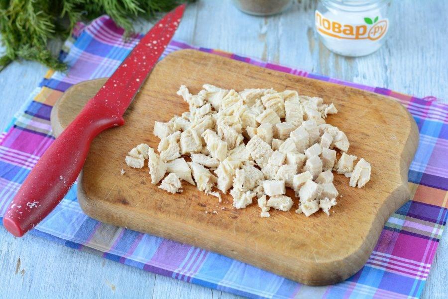 Сварите куриное филе в подсоленной воде и остудите. Варите примерно 20-25 минут. Мясо остудите и нарежьте небольшими кубиками.