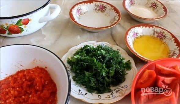 2. Помидоры вымойте, нарежьте на 4 части. Измельчите зелень. Очищенный чеснок, сладкий и острый перец пропустите через мясорубку или измельчите в блендере.