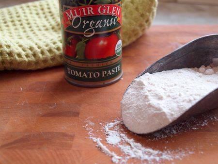Добавьте, помешивая, к луку муку и томаты.