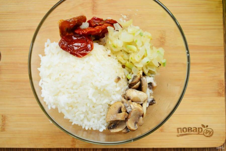 Лук измельчите, пассеруйте на разогретом масле до румяности. Грибы нарежьте ломтиками, добавьте на сковороду, обжарьте, посолите, поперчите. Соедините в миске рис, грибы, лук и вяленые томаты.