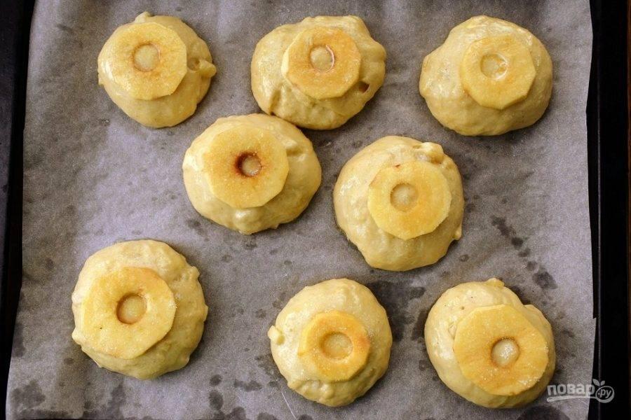 Яблоко очистите, удалите сердцевину, нарежьте тонкими кольцами. Разместите их на верх каждой заготовки, смажьте растопленным сливочным маслом и присыпьте сахаром. Поставьте булочки в разогретую до 180 °C духовку запекаться на 35-40 минут.