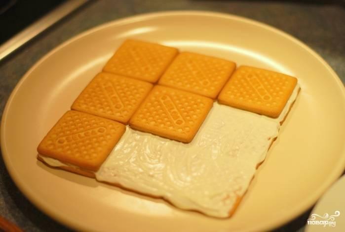 На плоском блюде начните сборку торта: первые два слоя (можно и первые три) смазывайте сметаной с сахаром. Оставьте сметану для финальной обмазки торта.