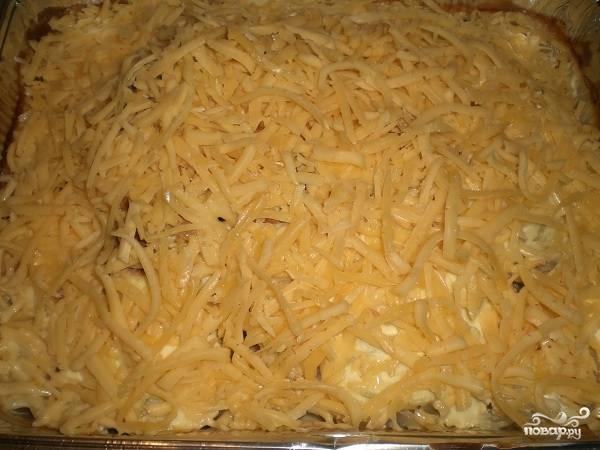 Затем достаем форму и засыпаем все натертым на средней терке сыром.