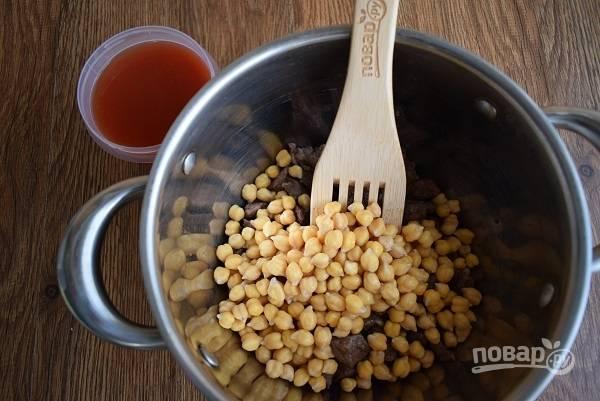 Добавьте нут, обжарьте до испарения жидкости, помешивая лопаткой. Затем добавьте горячую воду, доведите до кипения и тушите под закрытой крышкой около 1 часа.