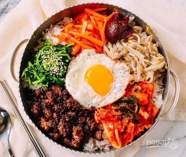 Отварите рис, разложите по тарелкам. Добавьте чили соус и сверху выложите все ингредиенты по краю тарелки. В центр положите обжаренное яйцо.