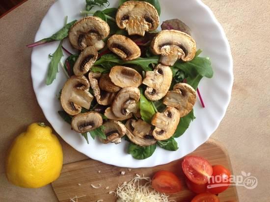 Поверх салатных листьев выложим грибы и сбрызнем их лимонным соком.