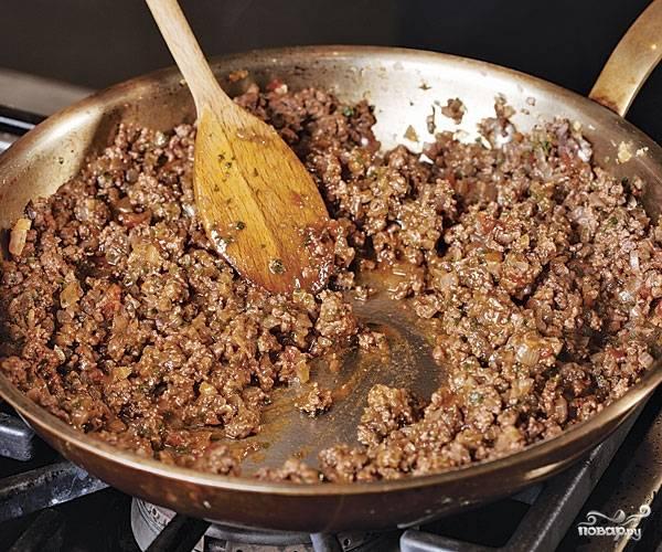 3. Для приготовления мясной начинки обжарьте в небольшом количестве оливкового масла мелко нарезанный лук. Добавьте фарш и жарьте, помешивая. Посолите, поперчите, добавьте красное вино, мускатный орех и немного томатной пасты. Все как следует перемешайте и тушите на среднем огне до готовности.