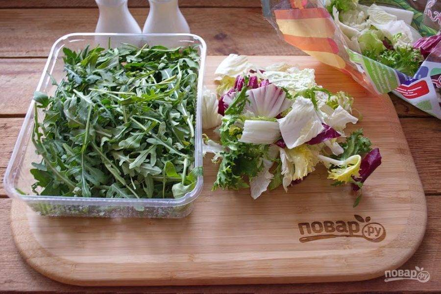 1. Для приготовления салата Адмиральский возьмите микс-салат и рукколу. Зелень промойте  и отжав и промокнув бумажным полотенцем воду поместите подготовленные листья в миску-салатник.