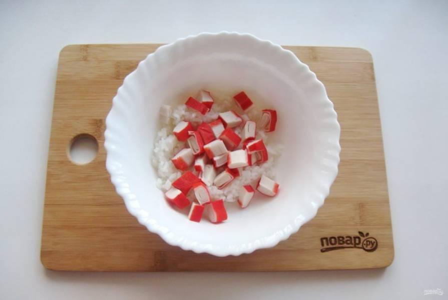 Крабовые палочки нарежьте и добавьте к рису. По желанию и наличию можно вместо палочек взять креветки.
