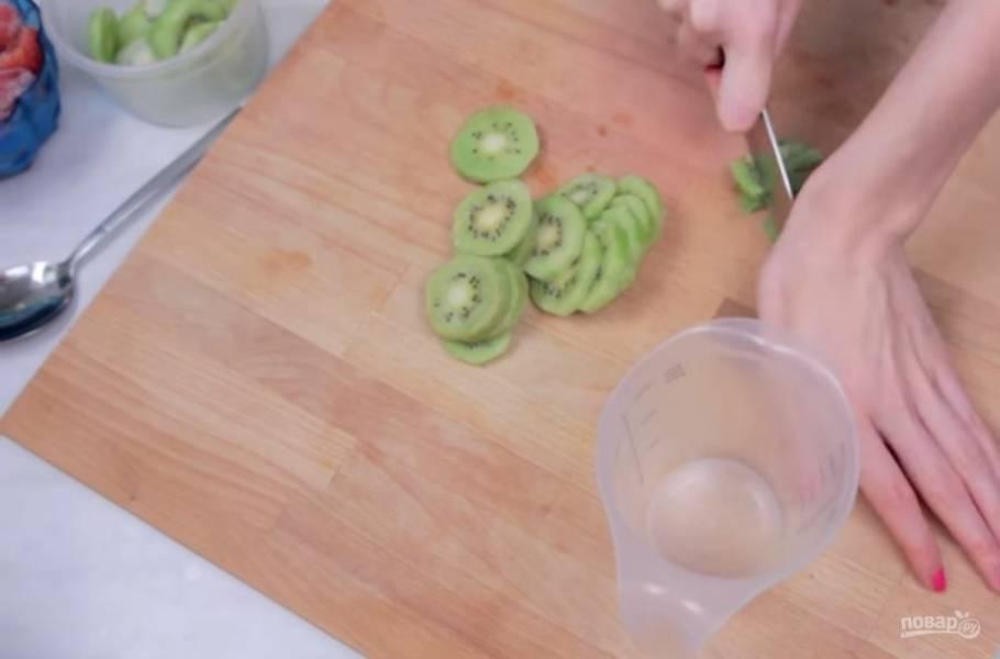 1. Для начала с помощью молоточка измельчите лед, завернув его в пакет и полотенце. Затем нарежьте мелкими кусочками замороженное киви и клубнику.